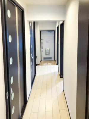 廊下。各部屋の扉はシックな落ち着いた色合いです。
