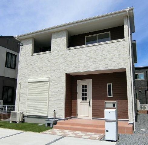 1号棟。ホワイト系の外壁サイディングにブラウンの玄関周りがアクセントになった外観です。