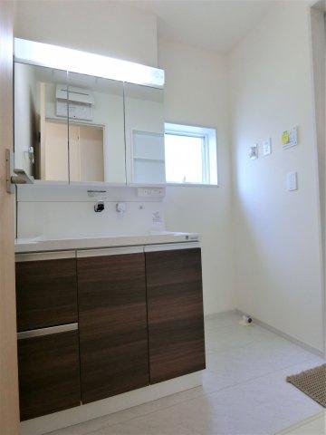 洗面脱衣室です。通常より大きく鏡裏の小物入れ、引き出しなど収納たっぷりの洗面台が嬉しい。