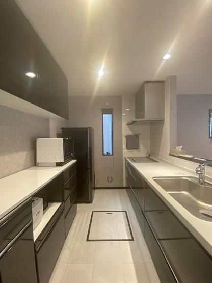 収納力が高いシステムキッチン、後ろには食器棚や吊戸棚が備わっておりたくさんの調理器具や食器が綺麗に片付きます。ゆとりあるキッチンスペースは、ご家族と一緒に並んでお料理やお菓子作りと楽しめます!