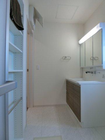 洗面脱衣室です。通常より大きく収納たっぷりの洗面台が嬉しい。壁面に棚も設置されています。