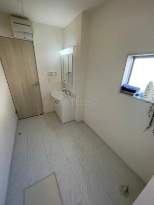 三面鏡付きの洗面台には鏡の裏に収納があり、すっきり片付けられます。 洗髪も可能な伸縮機能つきシャワーヘッドです。 着替えの棚も楽々置けるスペースがあります。
