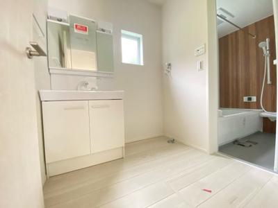 (写真は3号棟)清潔感のある白を基調とした洗面室は小窓からの採光で明るく、風通しがいいので湿気対策も考慮されています。シンプルな洗面台は収納力だけでなくシンクも広いです。
