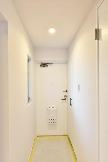 白を基調とした明るい玄関 人感センサー照明を設置