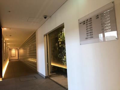 エレベーターに続くアプローチ。ガラスブロックやエレベーター前の床に施された石材にはデザイン性があり暖色の間接照明と相まってお洒落な空間となっております。