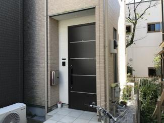 落ち着いた色調の玄関ドアのお住まい。家族の帰りを迎えます。