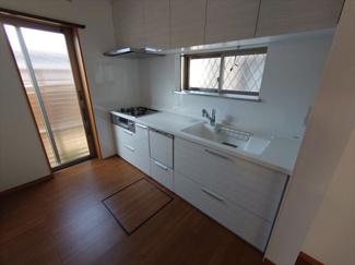 出窓と勝手口のあるキッチンは風通しが良いです。システムキッチンには食器洗い乾燥機もついております。天板とシンクのつなぎ目がないタイプでお手入れも簡単です。