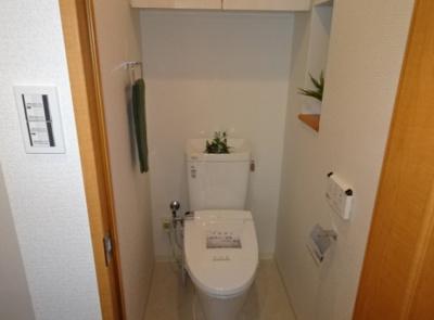 温水洗浄便座を設置したお手洗い。背面の吊戸棚や壁面の飾り棚など、使い勝手の良い空間となっております。