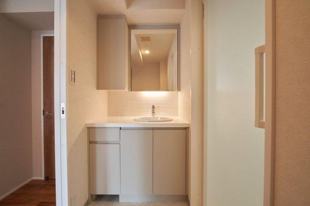 タイルを基調とした清潔感のある洗面化粧台。収納スペースがたっぷり設けられています