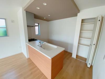 (同仕様写真)清潔感のあるシステムキッチンは対面タイプだからキッチン内にいながらご家族やお客様との会話が楽しめますね。平面には収納スペースを設けているので増えがちな小物も整理できます。