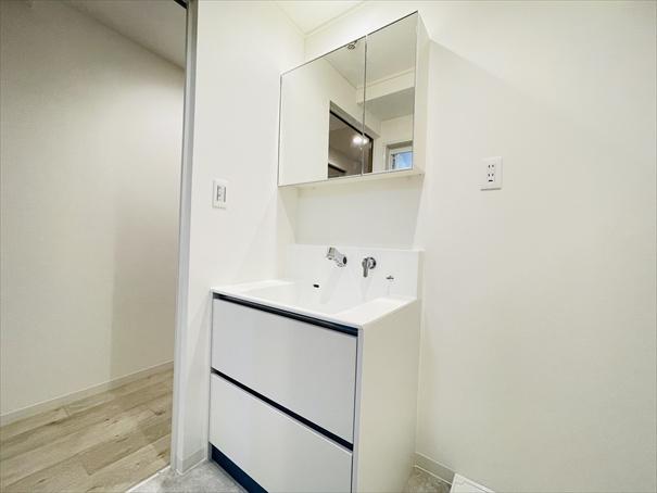 三面鏡裏収納付で、散らかりがちな洗面回りもすっきりと片付きます。 洗面台は、蛇口が壁についている最新タイプ。水が飛び散りにくくお掃除も楽々なんです