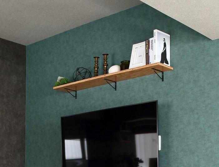 壁掛けテレビの背面のクロスは紀元前から生産されている織物調モチーフ。シンプルな柄は少しムラのある緑のクロスで柔らかい印象。