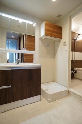 三面鏡洗面台は収納もたっぷり。洗濯機置場にも収納があります。