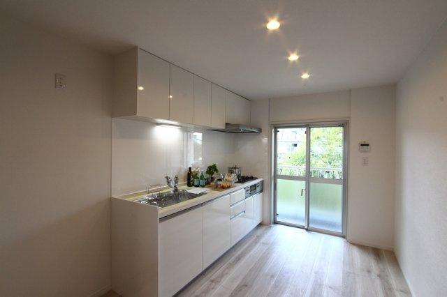 上部ダウンライトで天井がすっきりと高く見えます。 ホワイトで統一されたシステムキッチンは清潔感があり、お料理を作るのも楽しくなりそう♪