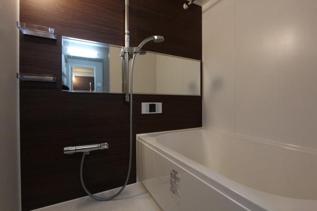 新規交換のユニットバス。ナチュラルな雰囲気になる木目調の壁でゆったり落ち着いたバスタイムになりそう。便利な浴室換気乾燥暖房機付きになっています。