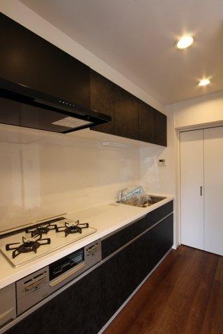 シックで落ち着いた雰囲気のシステムキッチンは3口コンロで家事効率も上がります。 収納たっぷりで、奥には可動棚付きのパントリーがありストックなどの保管に便利です。
