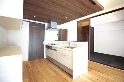 キッチンスペースは、折下げ天井が木目でお洒落なスペース。キッチンから洗面室に直通の便利な家事動線。