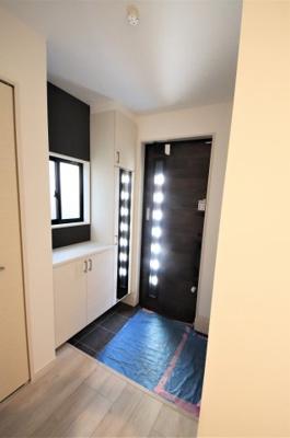 玄関。シックなダークブラウンの扉が印象的です。ドアにも開口部があって光が入ってきます。