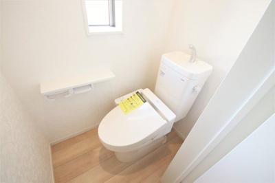 白を基調とした清潔感のあるトイレ。人感センサー付きで便座のフタが自動で開閉できるようになっています。